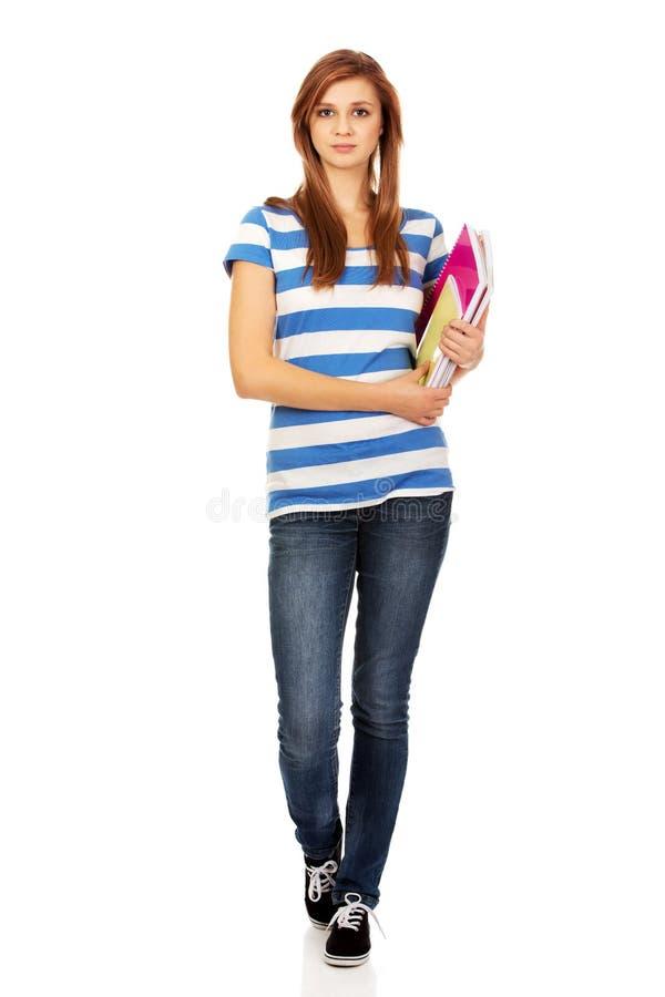 Femme adolescente de sourire de jeunes tenant des livres photo libre de droits