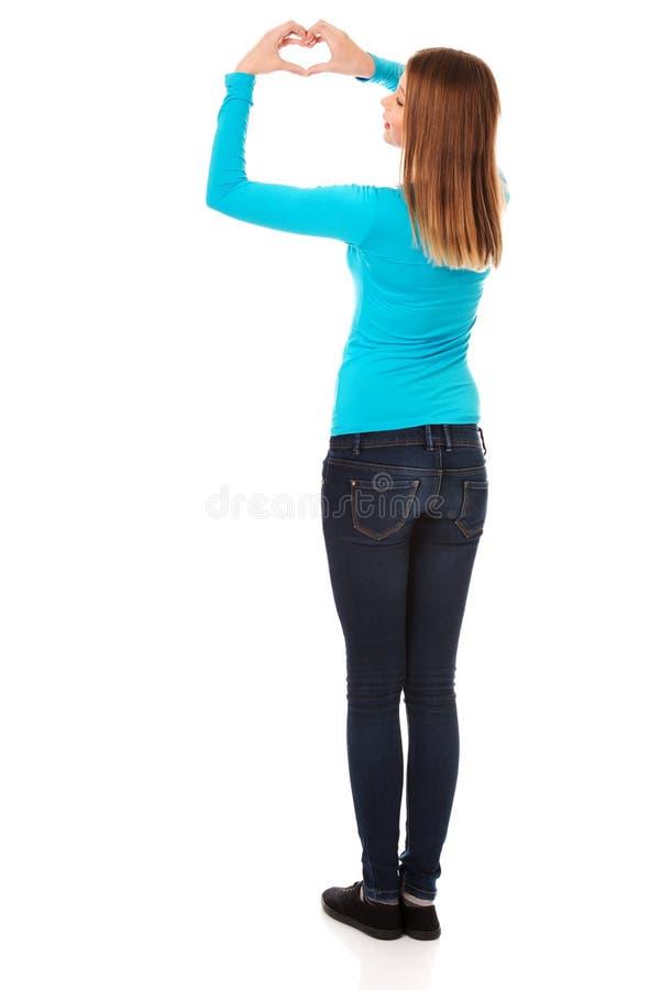 Femme adolescente de sourire faisant la forme de coeur photographie stock