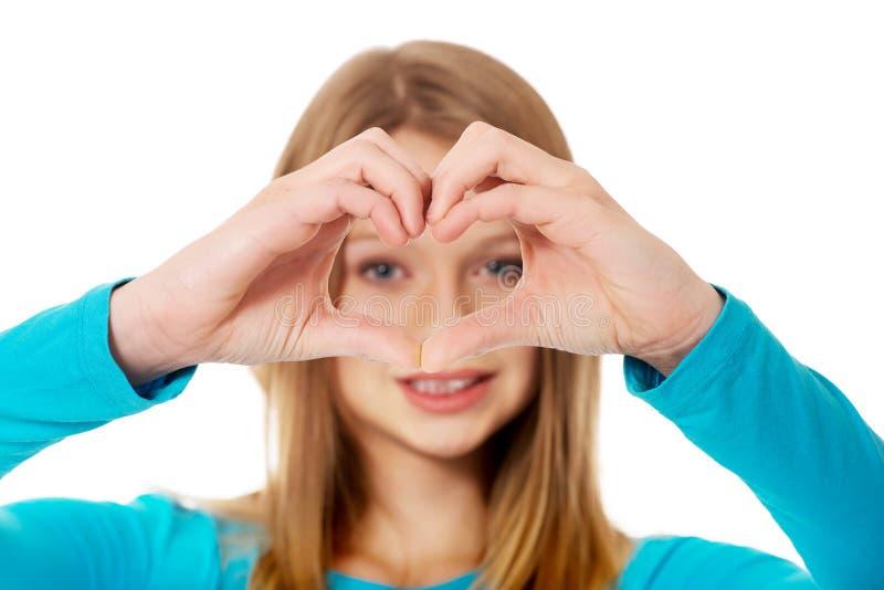 Femme adolescente de sourire faisant la forme de coeur photographie stock libre de droits