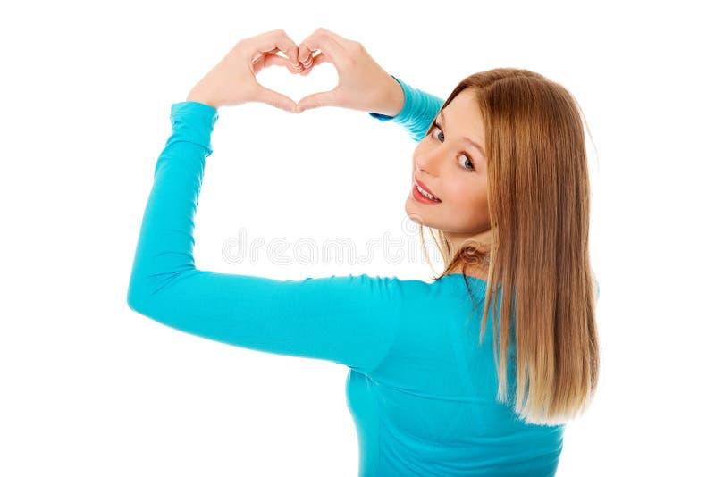 Femme adolescente de sourire faisant la forme de coeur photo stock