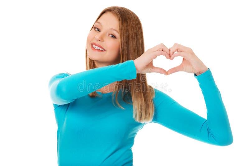 Femme adolescente de sourire faisant la forme de coeur photos stock