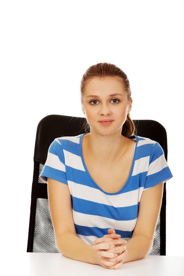 Femme adolescente de sourire s'asseyant derrière le bureau photo libre de droits