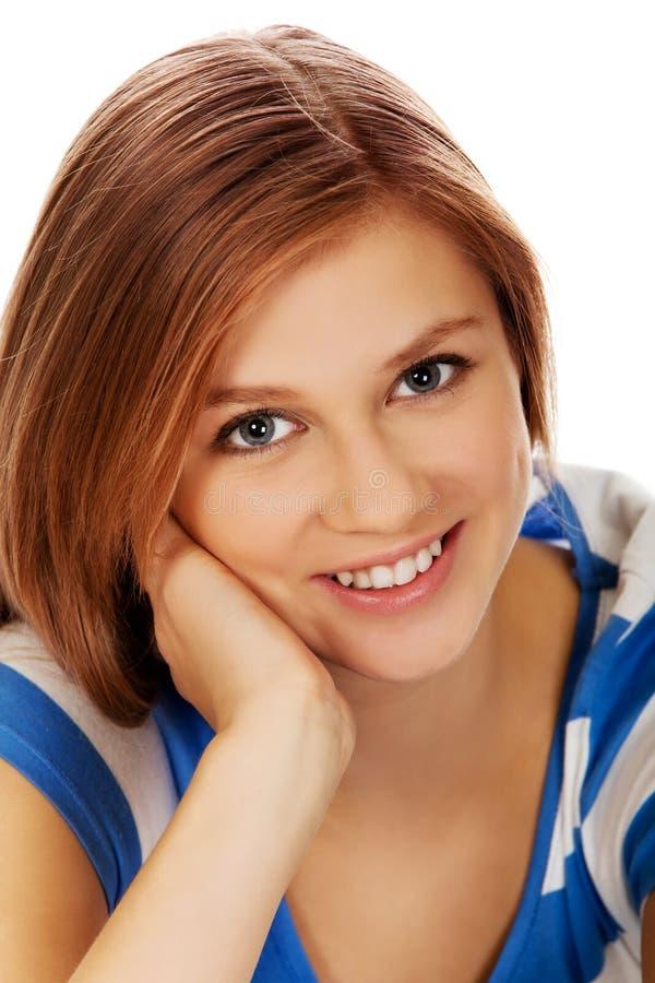 Femme adolescente de sourire s'asseyant sur un plancher image libre de droits