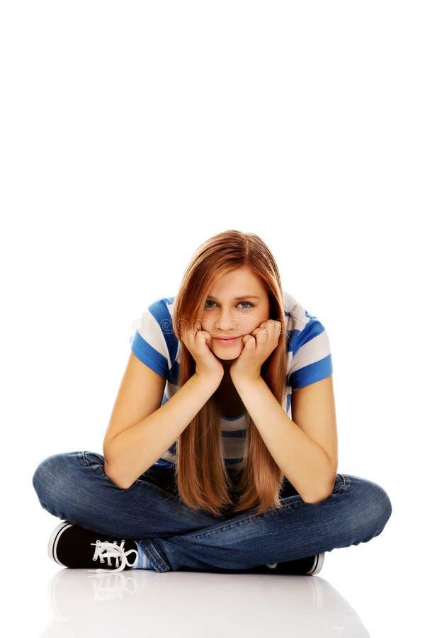 Femme adolescente de sourire s'asseyant sur un plancher avec des jambes croisées images libres de droits