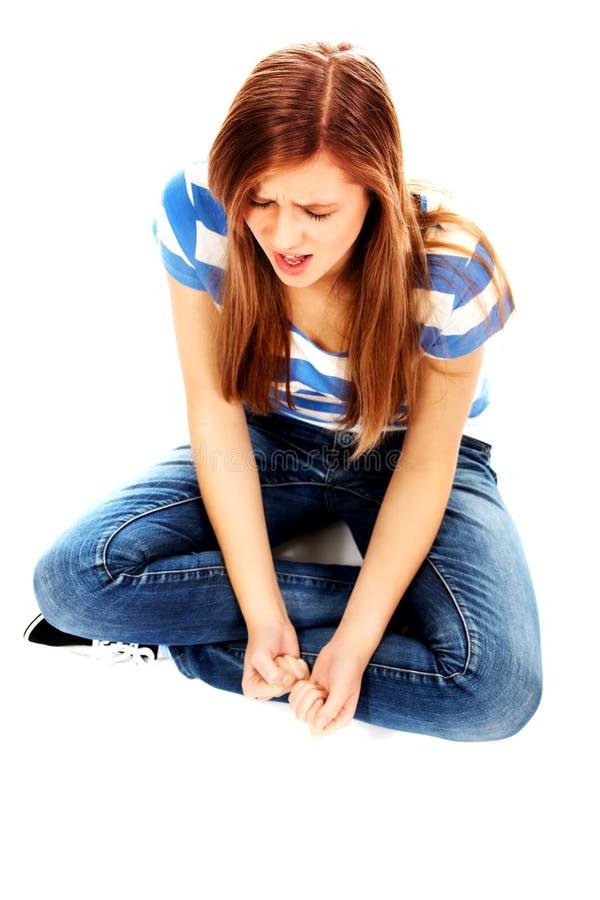 Femme adolescente fâchée s'asseyant sur le plancher et criant photos libres de droits