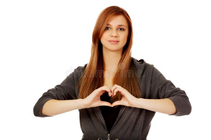 Femme adolescente faisant la forme de coeur avec ses mains images libres de droits