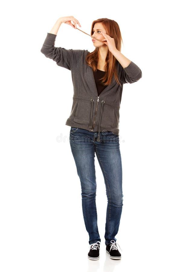 Femme adolescente faisant la moustache à partir des cheveux image stock