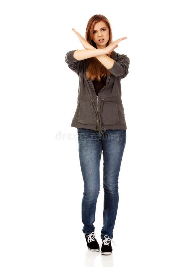 Femme adolescente faisant le signe d'arrêt avec les mains croisées images stock