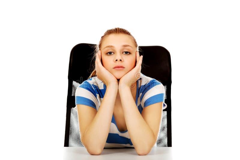 Femme adolescente fatiguée s'asseyant derrière le bureau photographie stock libre de droits