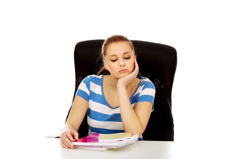 Femme adolescente fatiguée s'asseyant derrière le bureau photographie stock