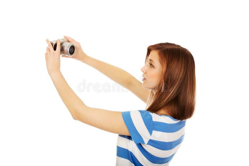 Femme adolescente heureuse prenant le selfie avec l'appareil-photo classique de slr photo stock