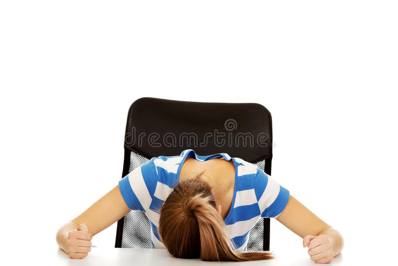 Femme adolescente inquiétée dormant au bureau image stock