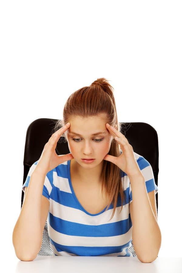 Femme adolescente inquiétée s'asseyant derrière le bureau photos stock