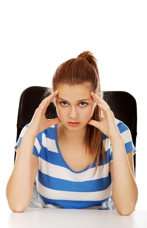 Femme adolescente inquiétée s'asseyant derrière le bureau image stock