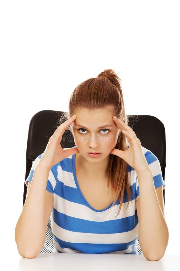 Femme adolescente inquiétée s'asseyant derrière le bureau images libres de droits