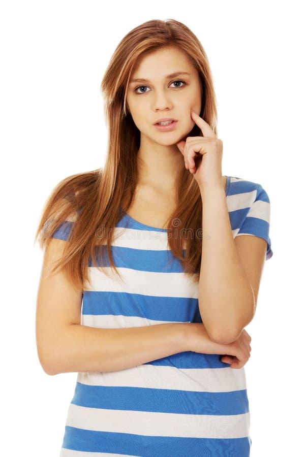 Femme adolescente songeuse avec le doigt sur la joue photos libres de droits