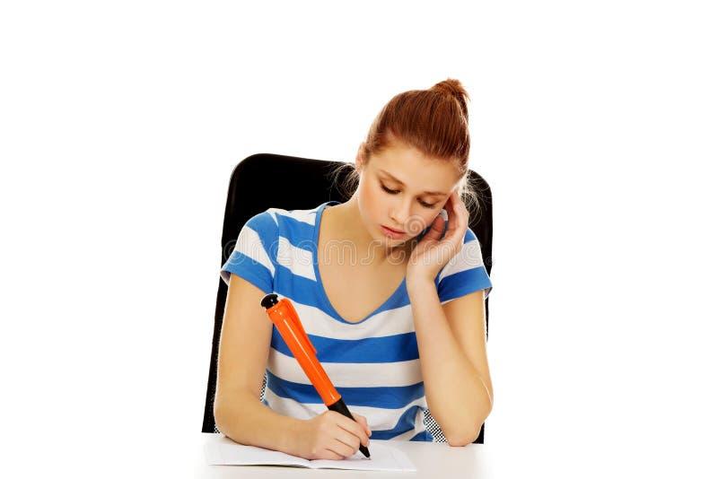 Femme adolescente songeuse faisant le travail images stock