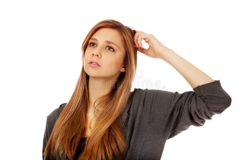 Femme adolescente songeuse rayant sa tête photos libres de droits