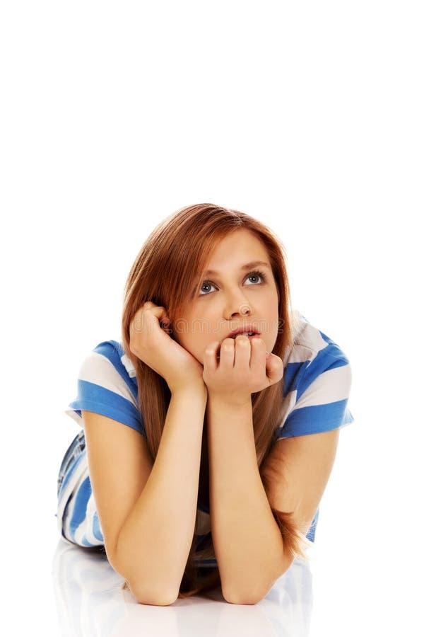 Femme adolescente songeuse se trouvant sur le plancher photo stock