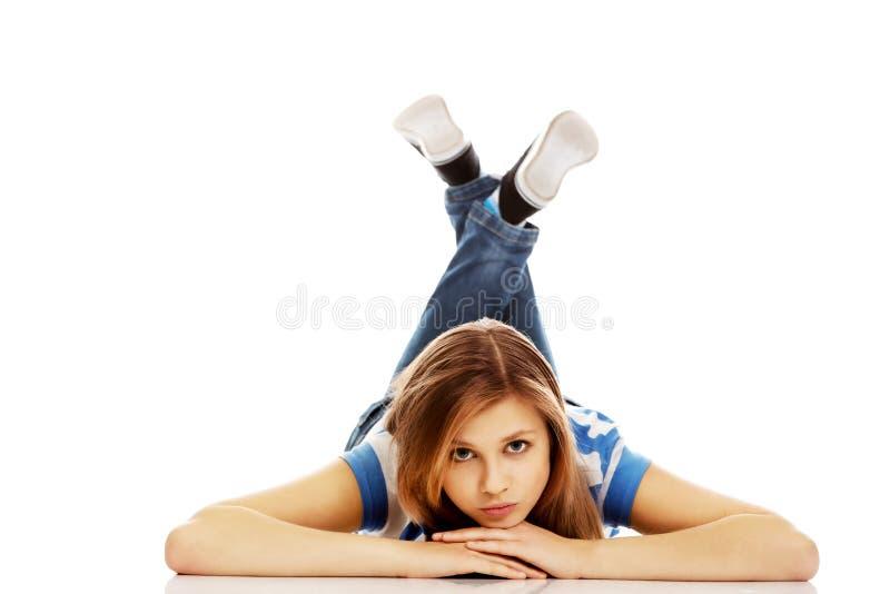 Femme adolescente songeuse se trouvant sur le plancher image stock