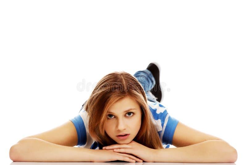 Femme adolescente songeuse se trouvant sur le plancher photographie stock