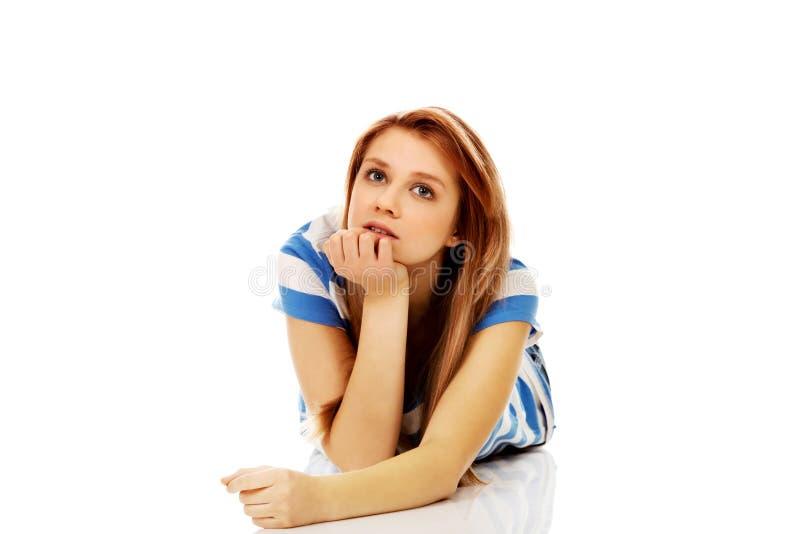 Femme adolescente songeuse se trouvant sur le plancher image libre de droits