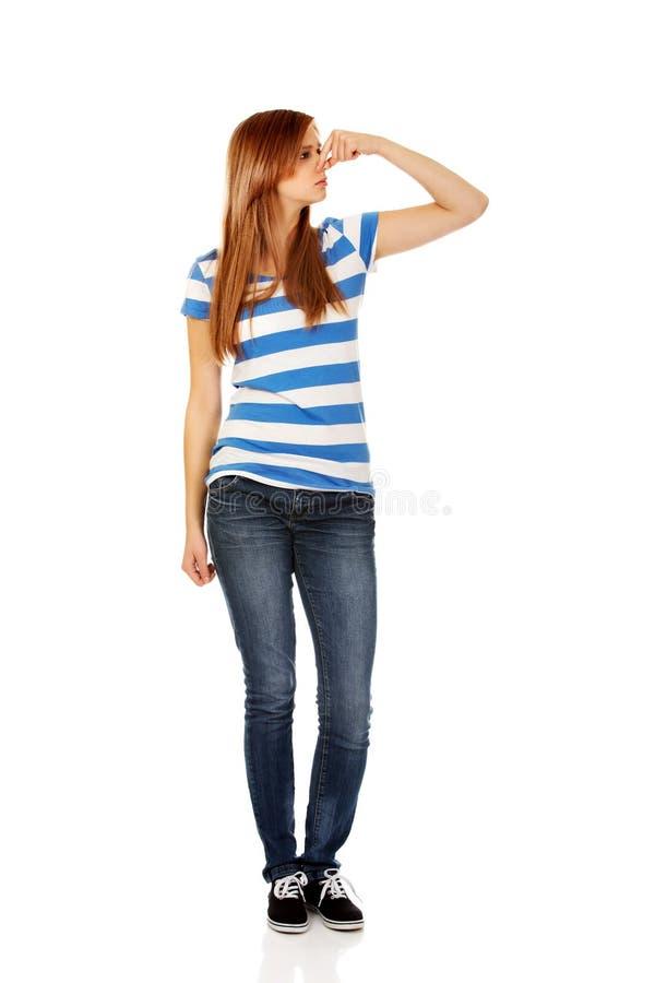 Femme adolescente tenant son nez en raison d'une mauvaise odeur photo stock