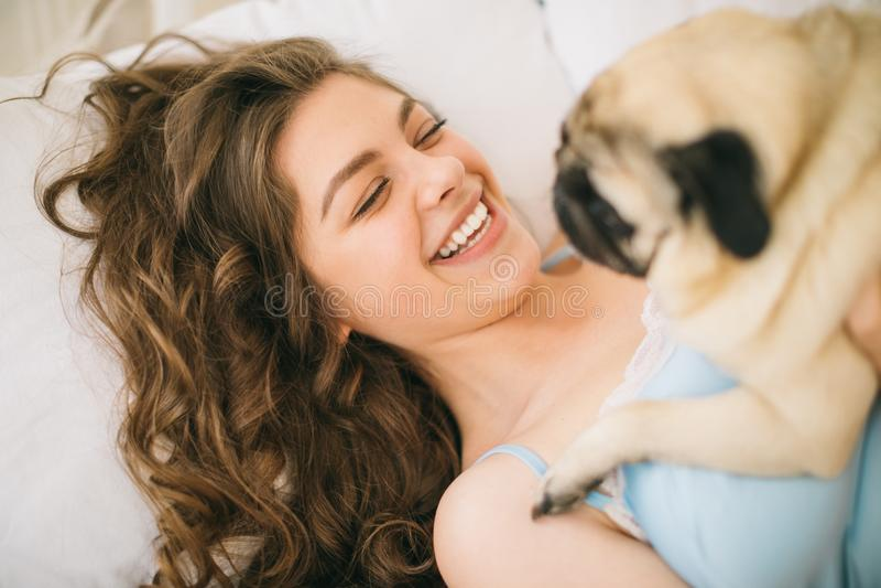 Femme adorable étreignant son chien de roquet dans le lit photos libres de droits