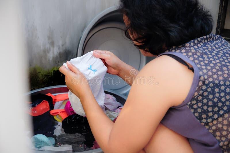 Femme adulte asiatique recherchant une certaine tache sur Cllothes pendant la blanchisserie images libres de droits