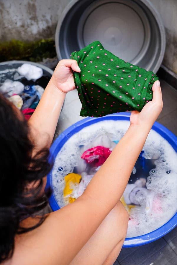 Femme adulte asiatique recherchant une certaine tache sur Cllothes pendant la blanchisserie photos stock