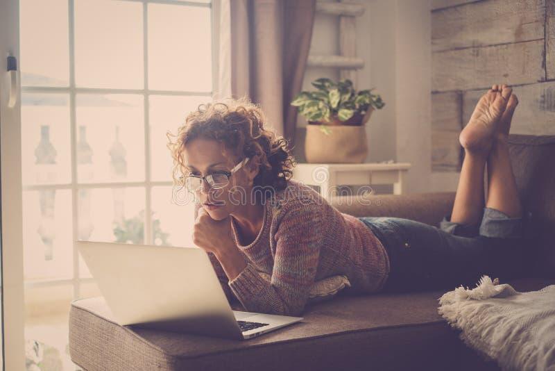 Femme adulte attirante de Moyen Âge employant la technologie d'Internet d'ordinateur portable à la maison pour des affaires ou le photos libres de droits