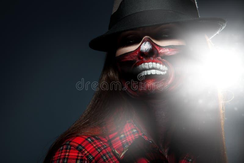 Femme adulte avec l'art effrayant de visage pour la nuit de Halloween regardant c photographie stock