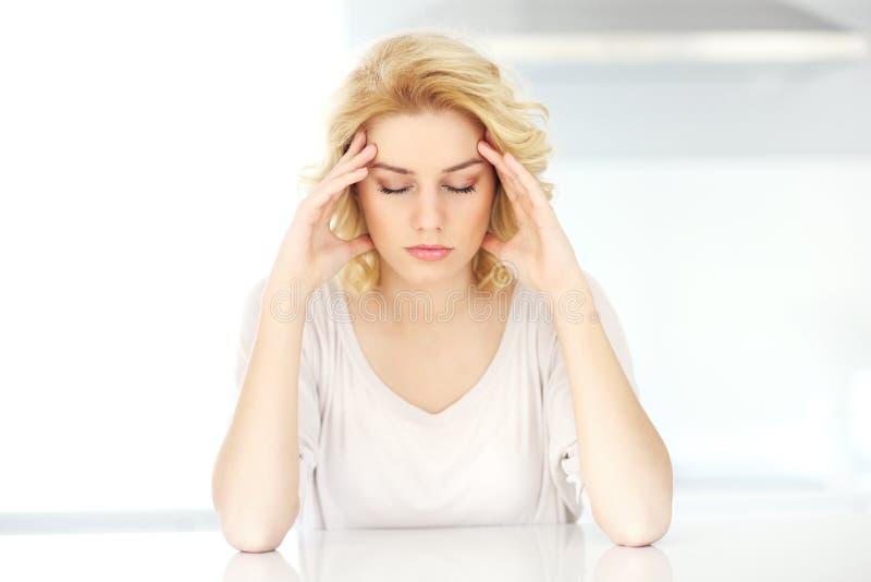 Femme adulte ayant le mal de tête à la maison images libres de droits