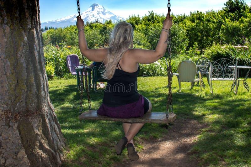 Femme adulte balançant sur une oscillation en bois d'arbre dans le Mt Capot Orégon Concept pour le bonheur, enfantin, innocence,  photographie stock libre de droits
