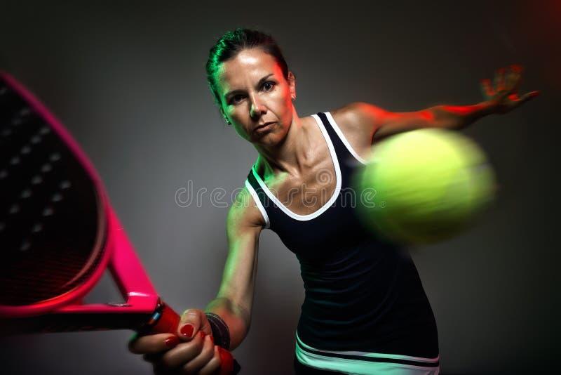 Femme adulte de forme physique jouant le padel d'intérieur D'isolement sur le noir photographie stock