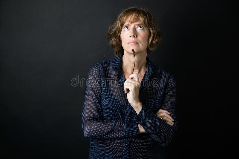 Femme adulte de Toughtful pensant sur ses inquiétudes au-dessus de fond noir photographie stock