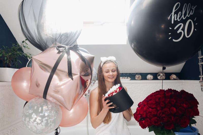 Femme adulte heureuse avec des fleurs et des ballons à air dans la salle de bains photo libre de droits