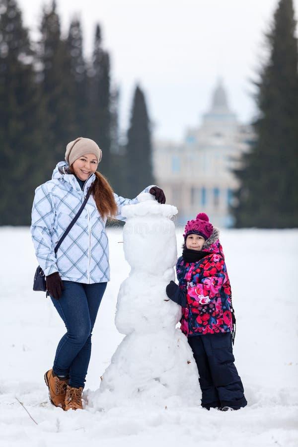 Femme adulte heureuse et souriante et jeune fille tenant le bonhomme de neige proche sur le champ hivernal du parc, horaire d'hiv photo stock