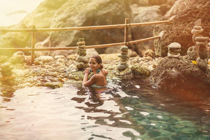 Femme adulte posant avec un sourire au soleil et une source thermale sur le fond des roches image libre de droits