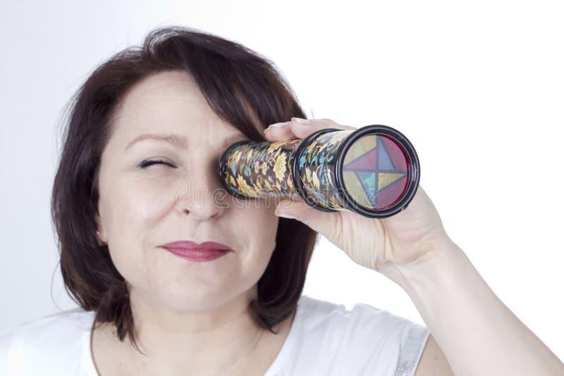 Femme adulte regardant dans un kaléidoscope photo stock