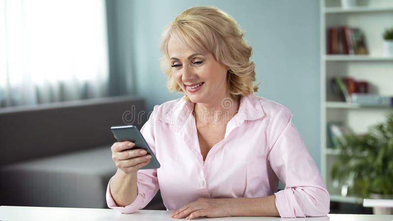 Femme adulte regardant des photos de ses enfants adultes avec la chaleur et amour images stock