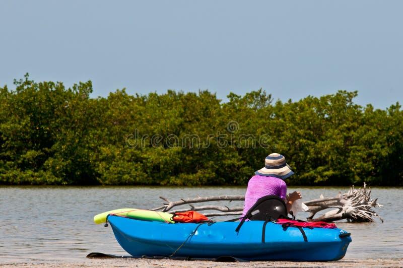 Femme adulte s'asseyant sur le kayak et mangeant le déjeuner photos libres de droits