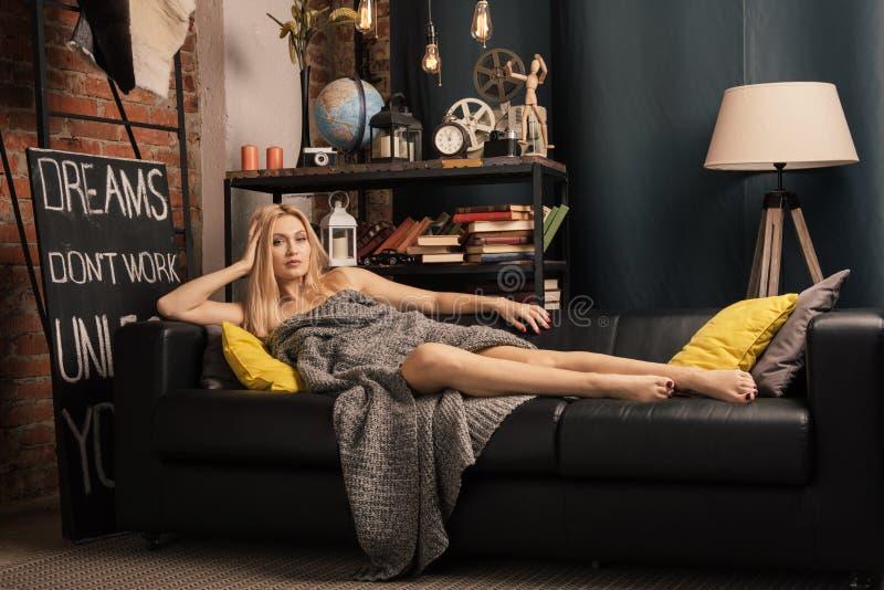 Femme adulte se trouvant sur le divan dans une couverture de laine dans la salle intérieure image libre de droits