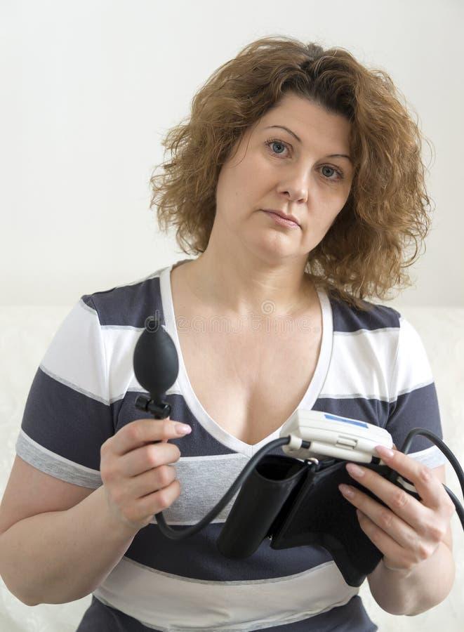 Femme adulte tenant le tonometer automatique pour la tension artérielle de mesure photo stock
