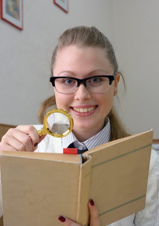 Femme affichant un livre avec la loupe photos libres de droits