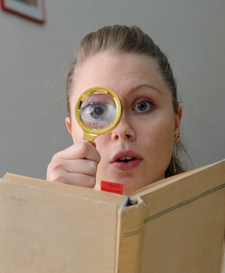 Femme affichant un livre avec la loupe image libre de droits