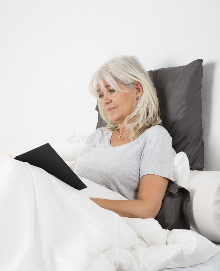 Femme affichant un livre dans le bâti images libres de droits