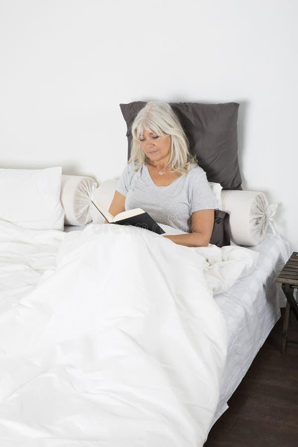 Femme affichant un livre dans le bâti photographie stock libre de droits