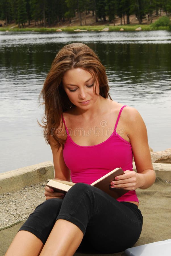 Femme affichant un livre par un lac photographie stock
