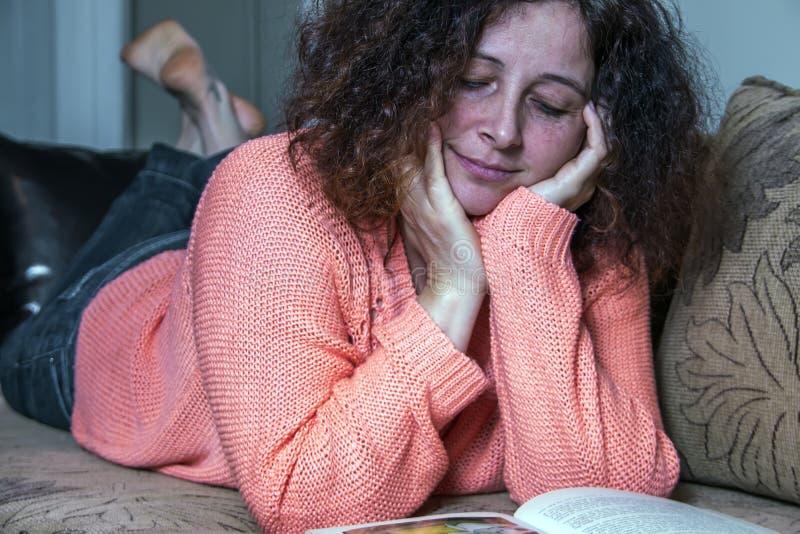 Femme affichant un livre sur le bâti photos stock